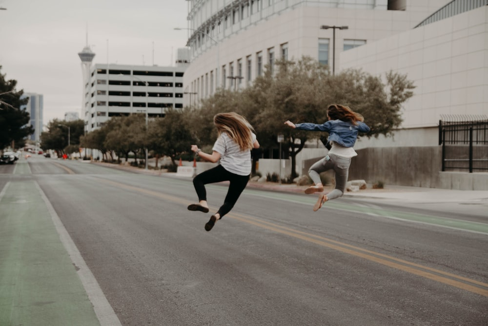 two woman jumping on the street during daytime
