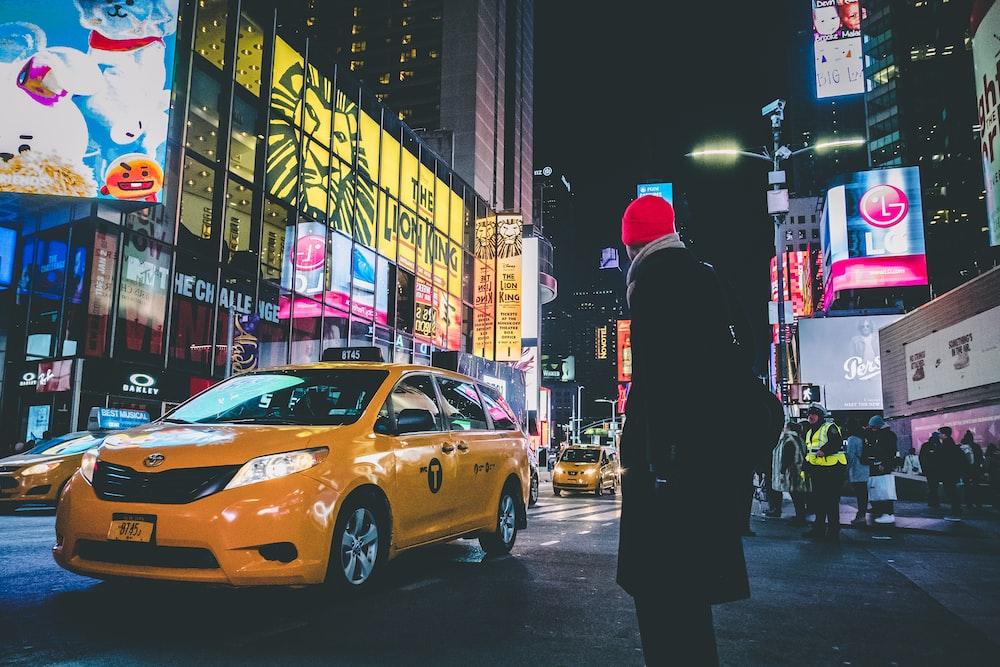 man wearing black coat standing near yellow taxi