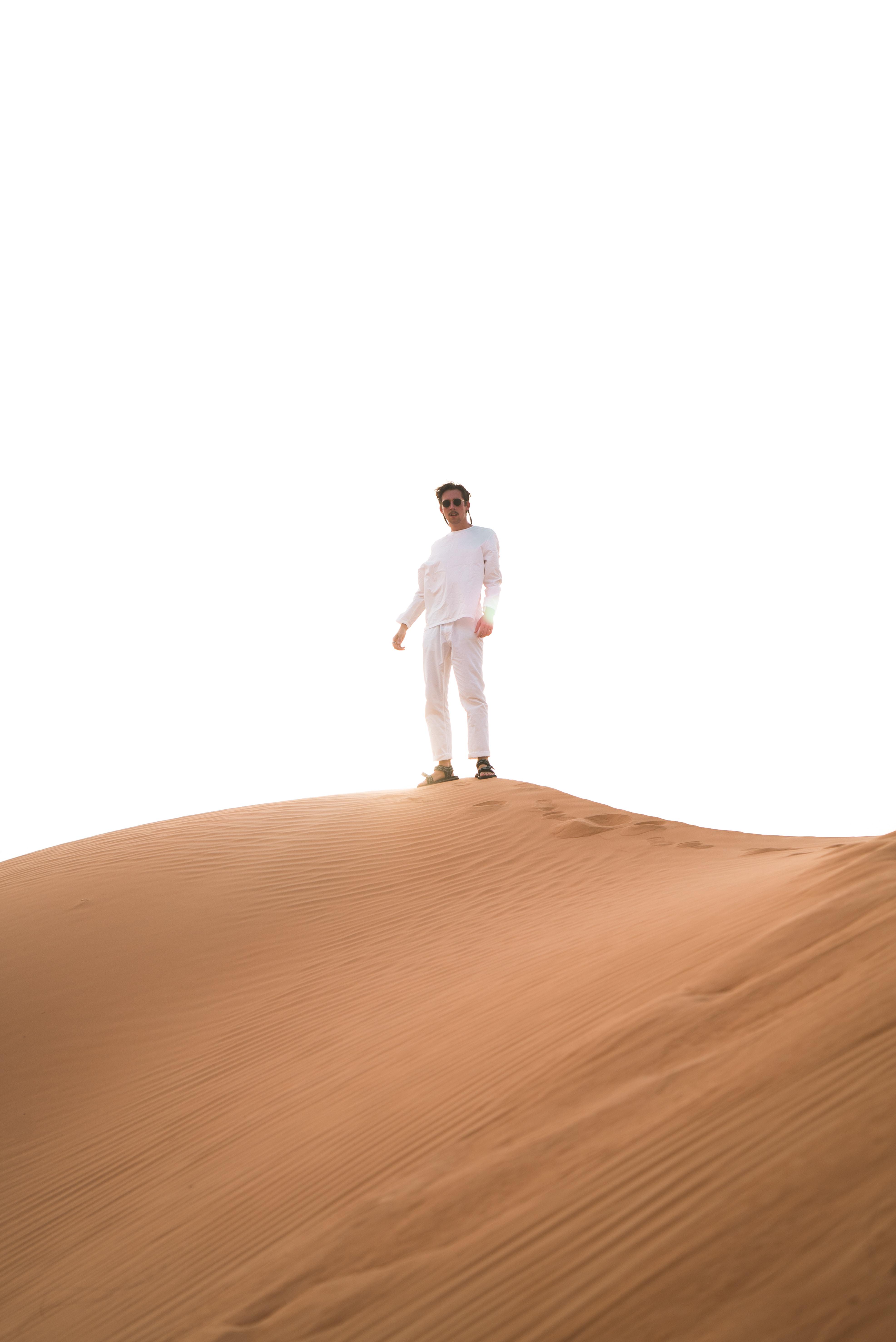 man standing atop desert sand dune