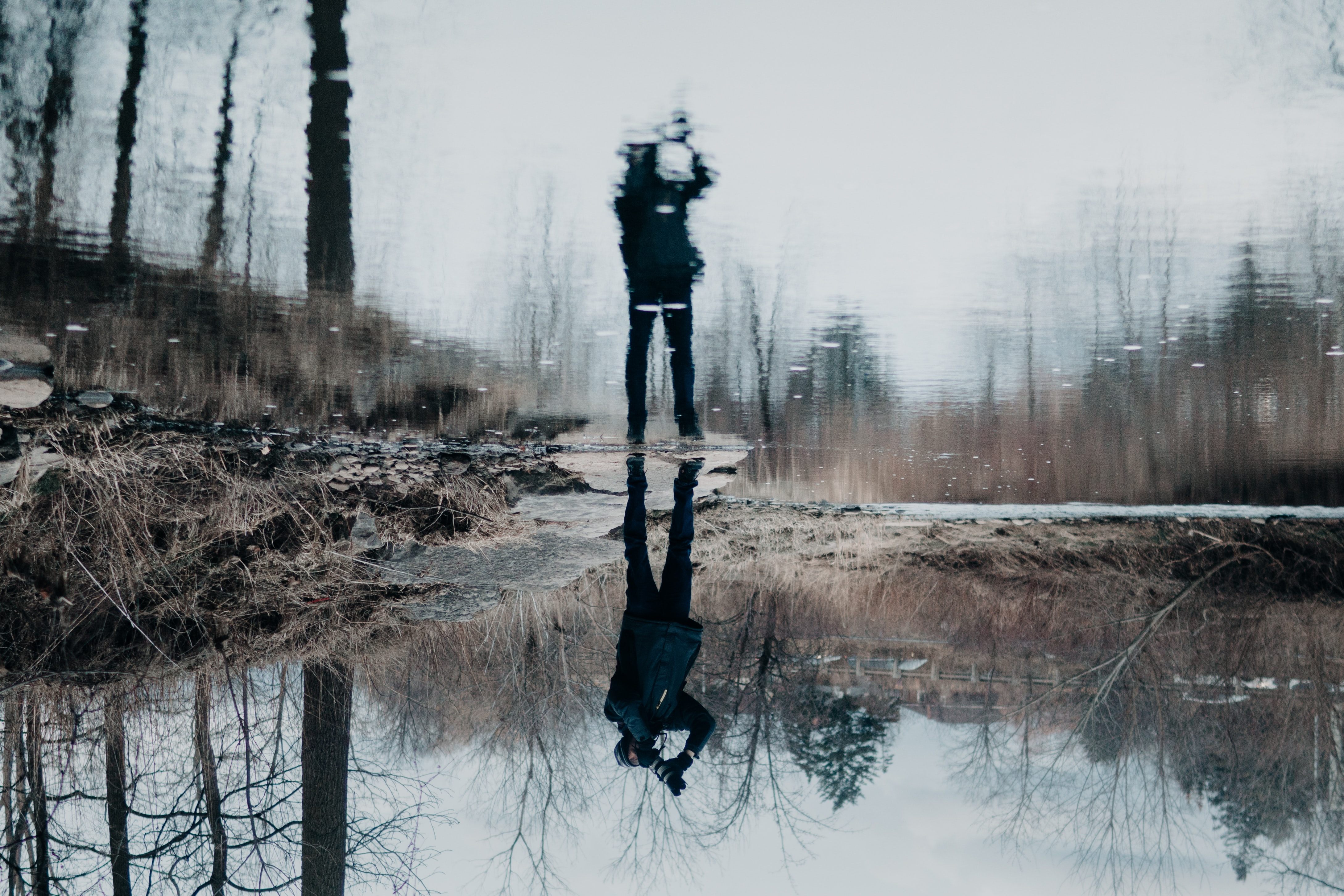 water reflection of a person holding camera standing near pond