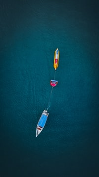 white and yellow boats on body of water