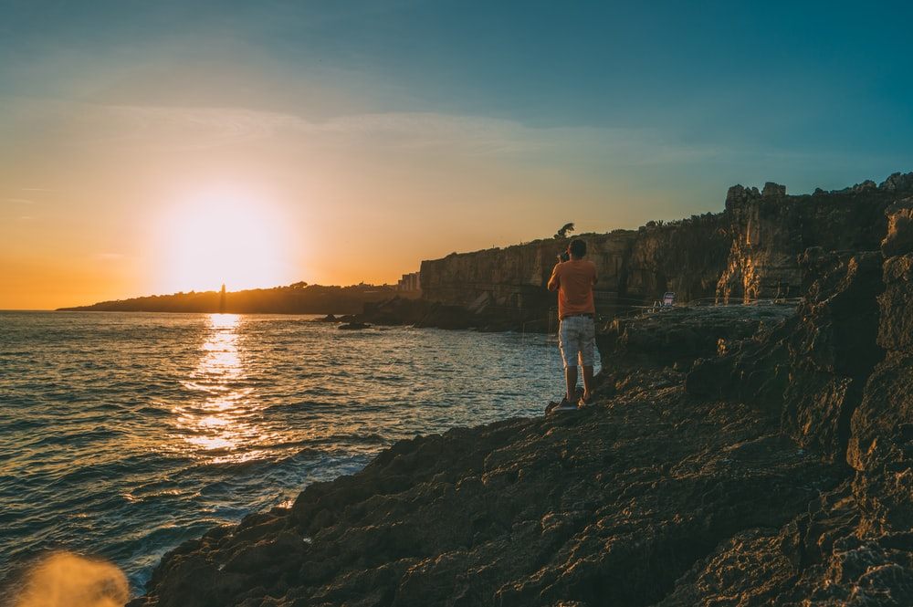 man standing on cliff beside body of water at daytime