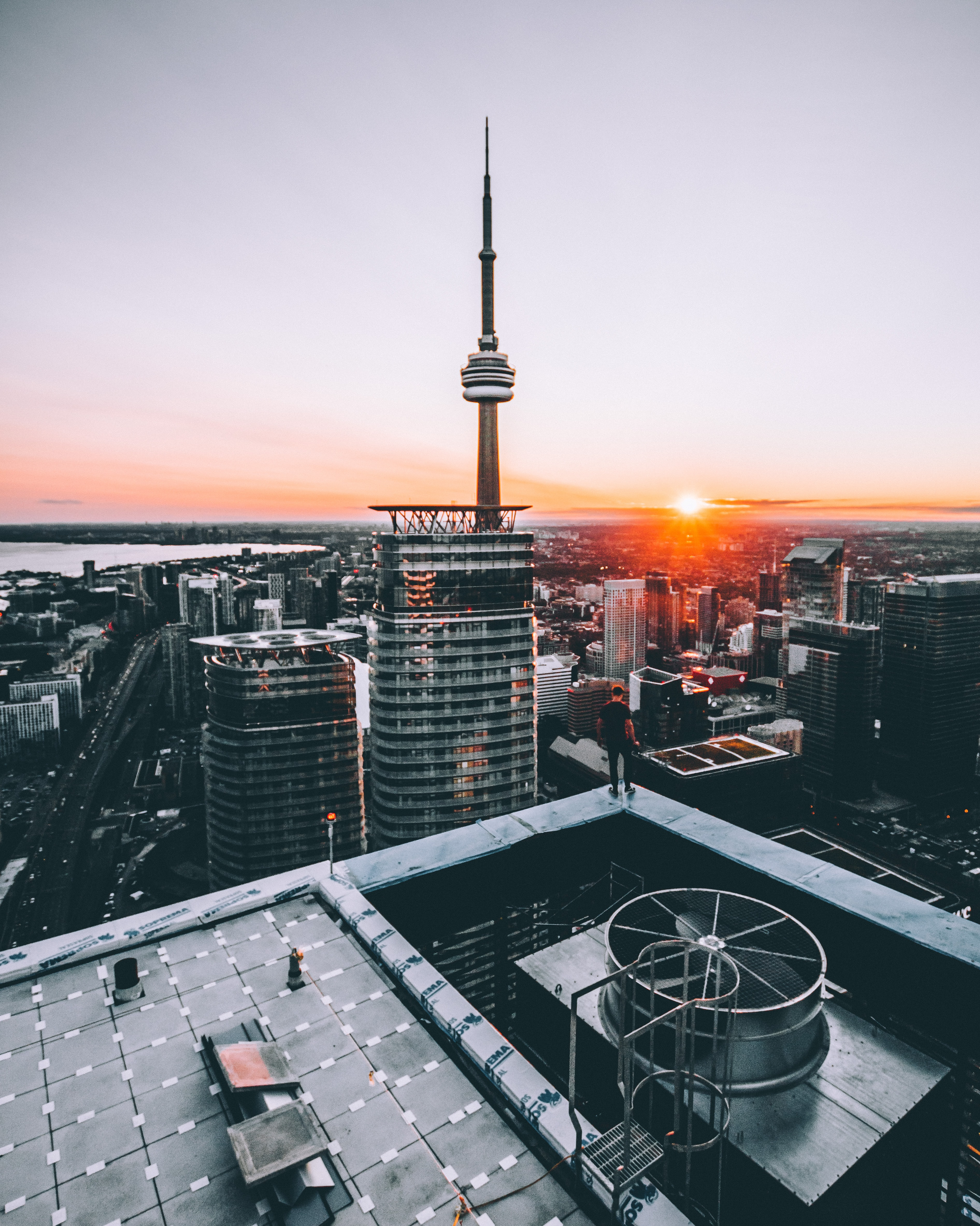 person standing on top of building in front of CN tower during sunset