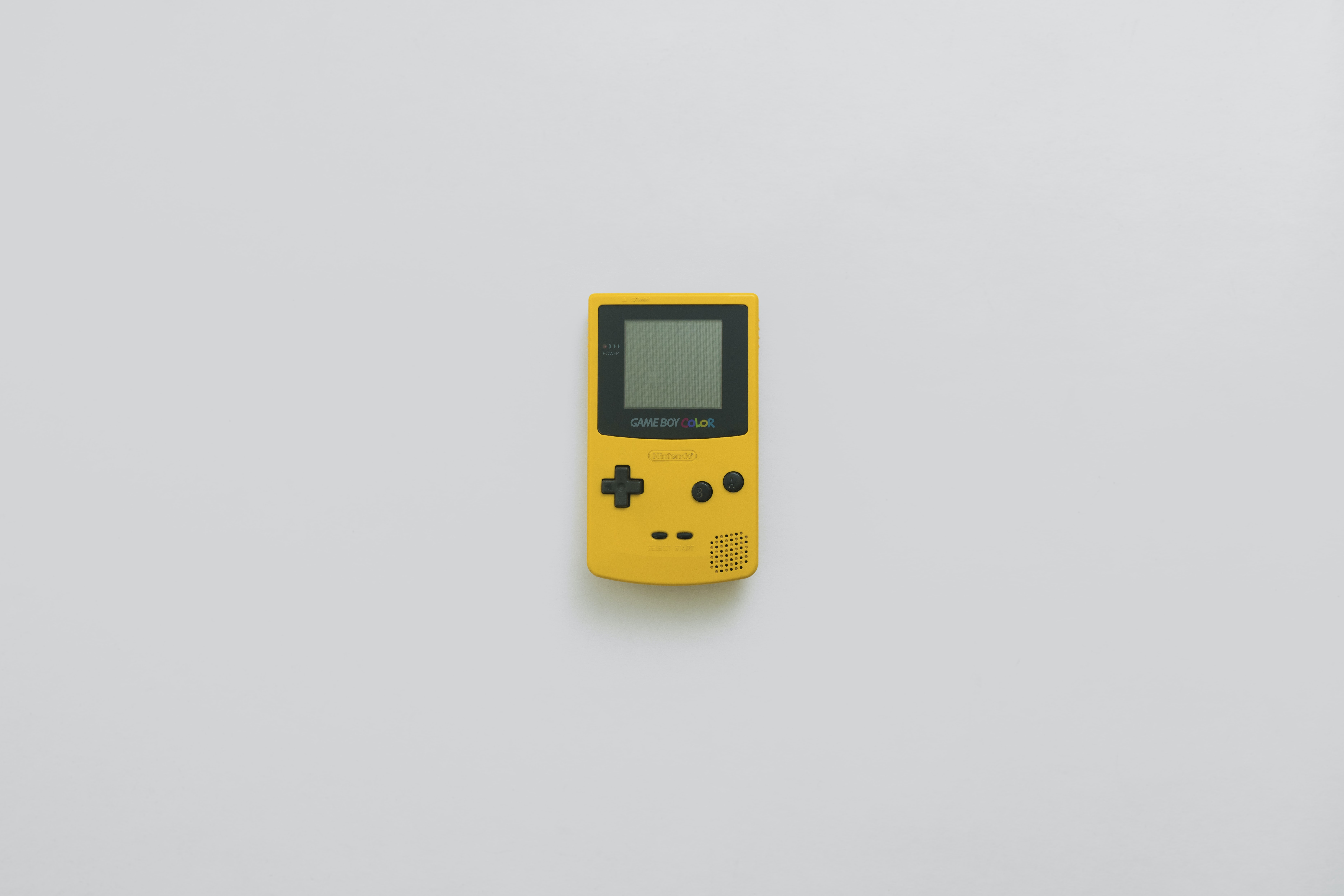 yellow Game Boy Color on table