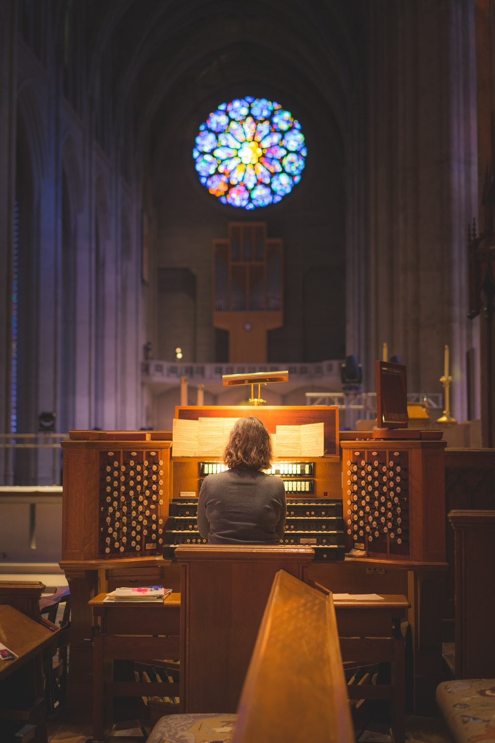 person sitting in front of church organ