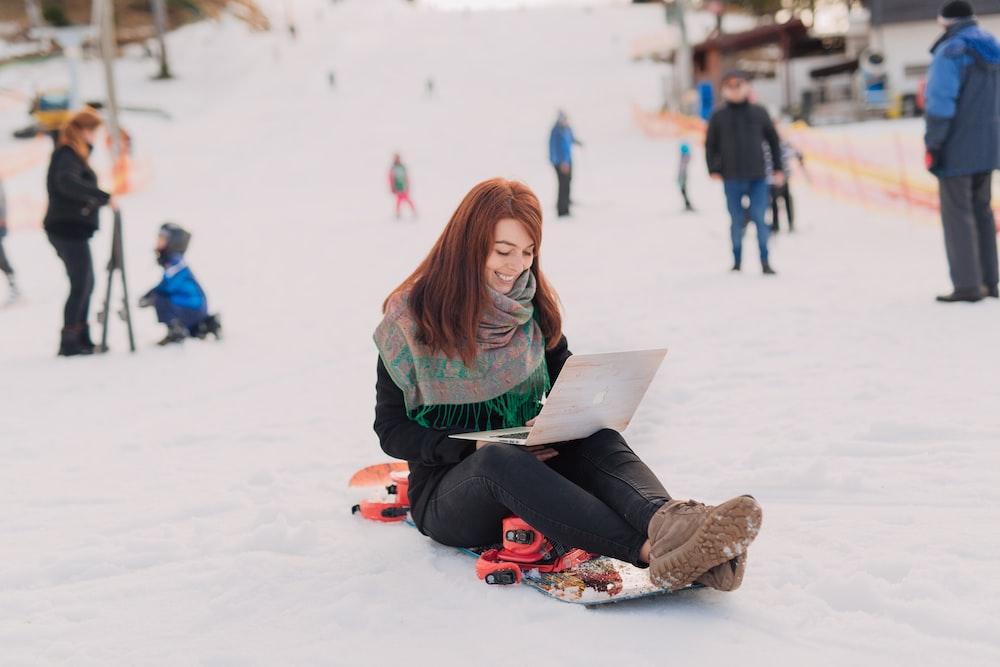 woman sitting on snowboard using MacBook Pro