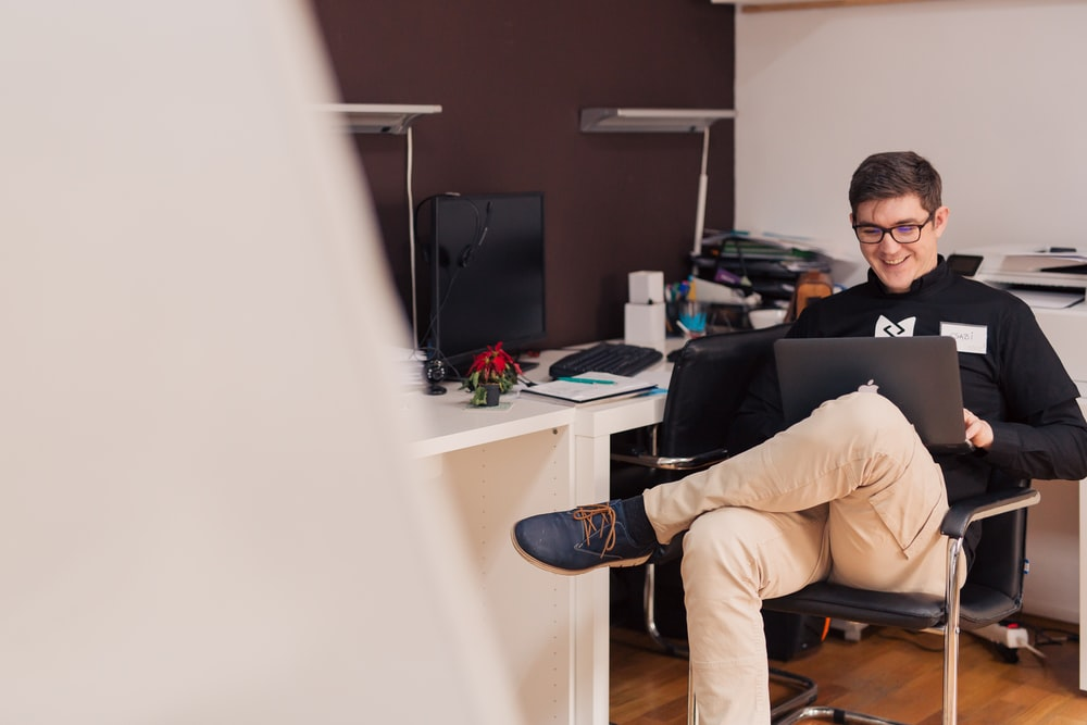 man smiling while sitting and using MacBook
