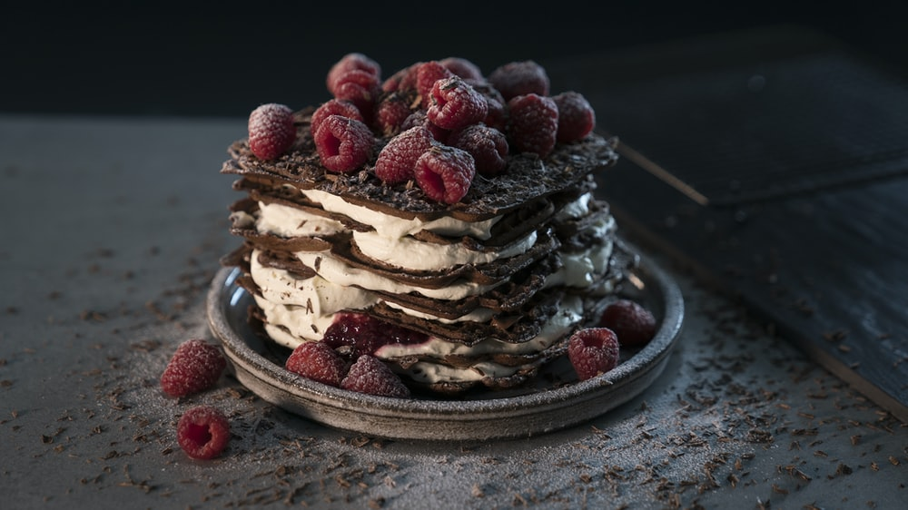 red raspberries on chocolate and cream cake