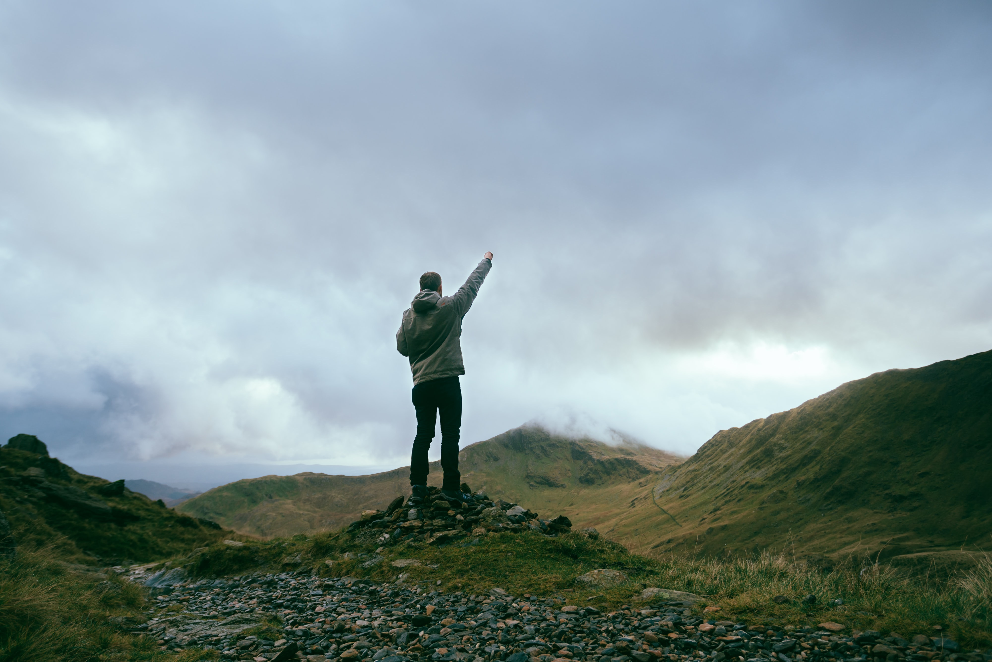 man standing on rocks near mountains pointing sky during daytime