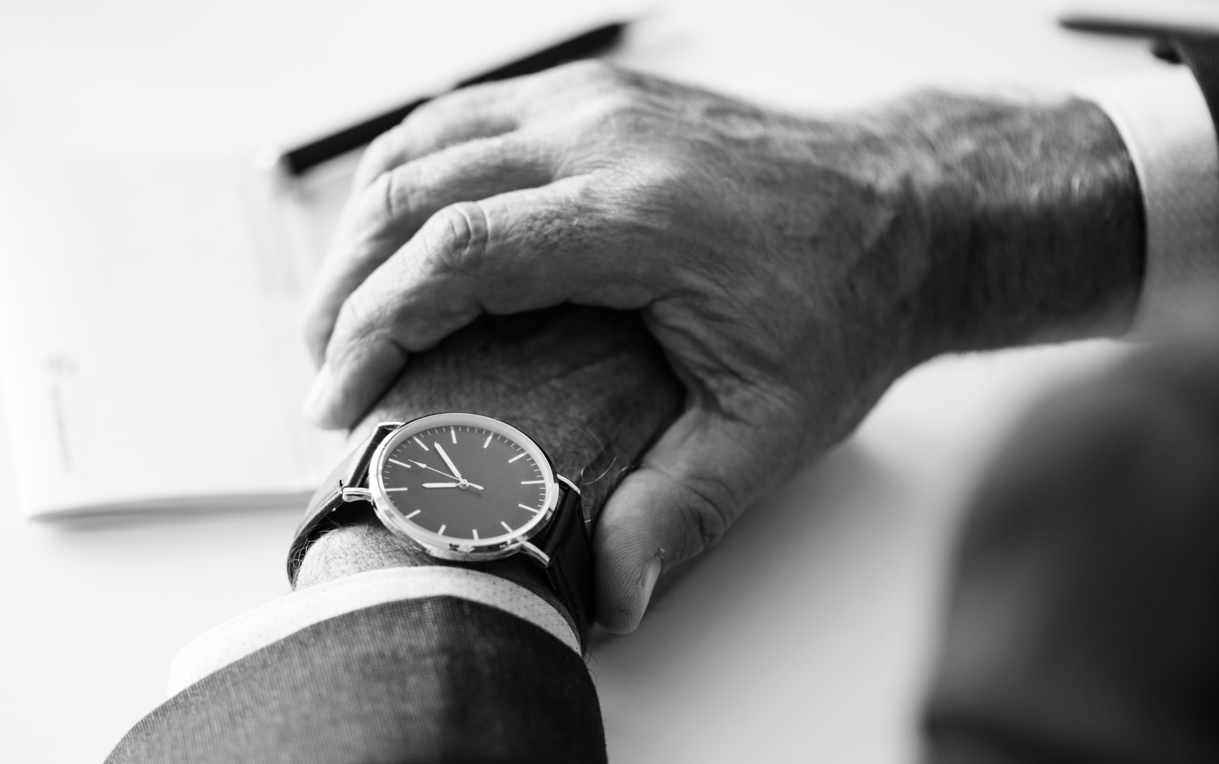 grayscale photography of person holding watch