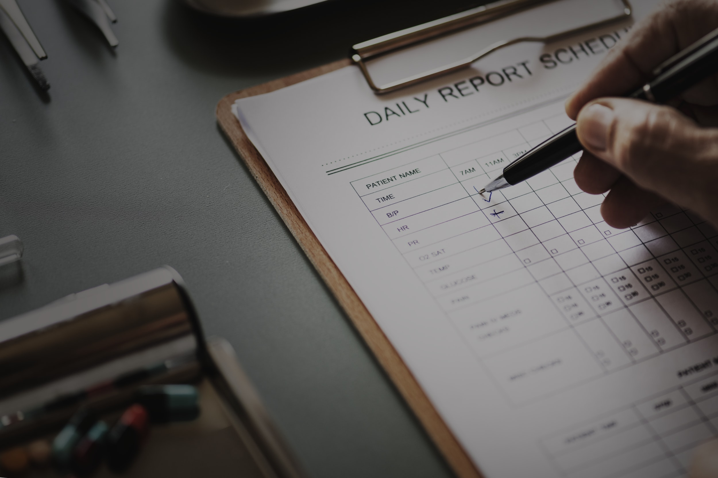 person writing on daily report schedule paper