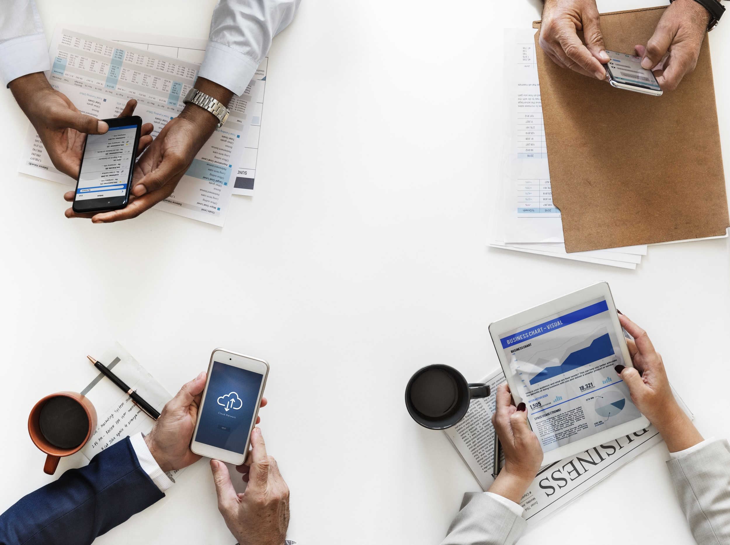flat lay photo of four person holding smartphone and book