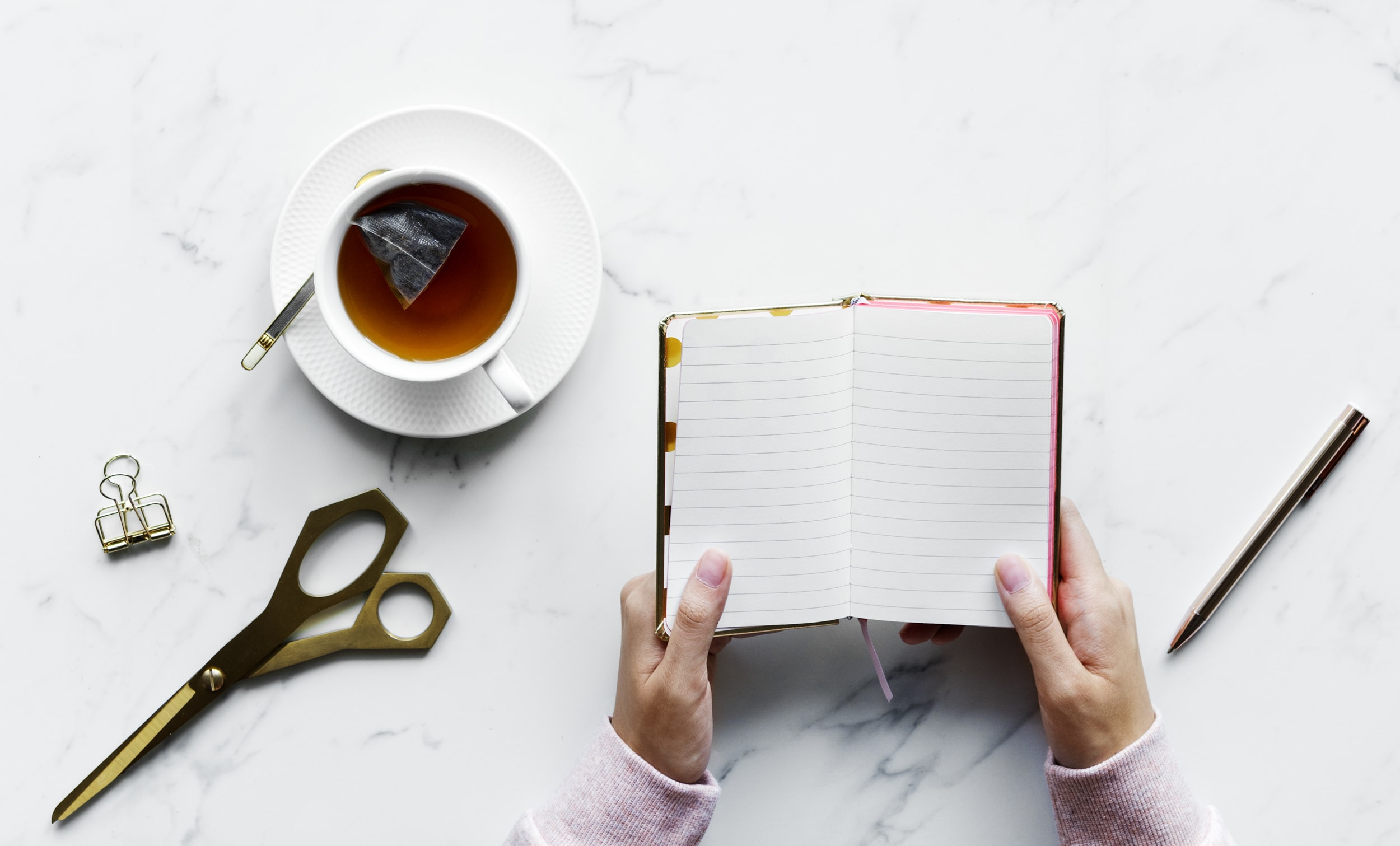 person holding notebook next to cup of coffee