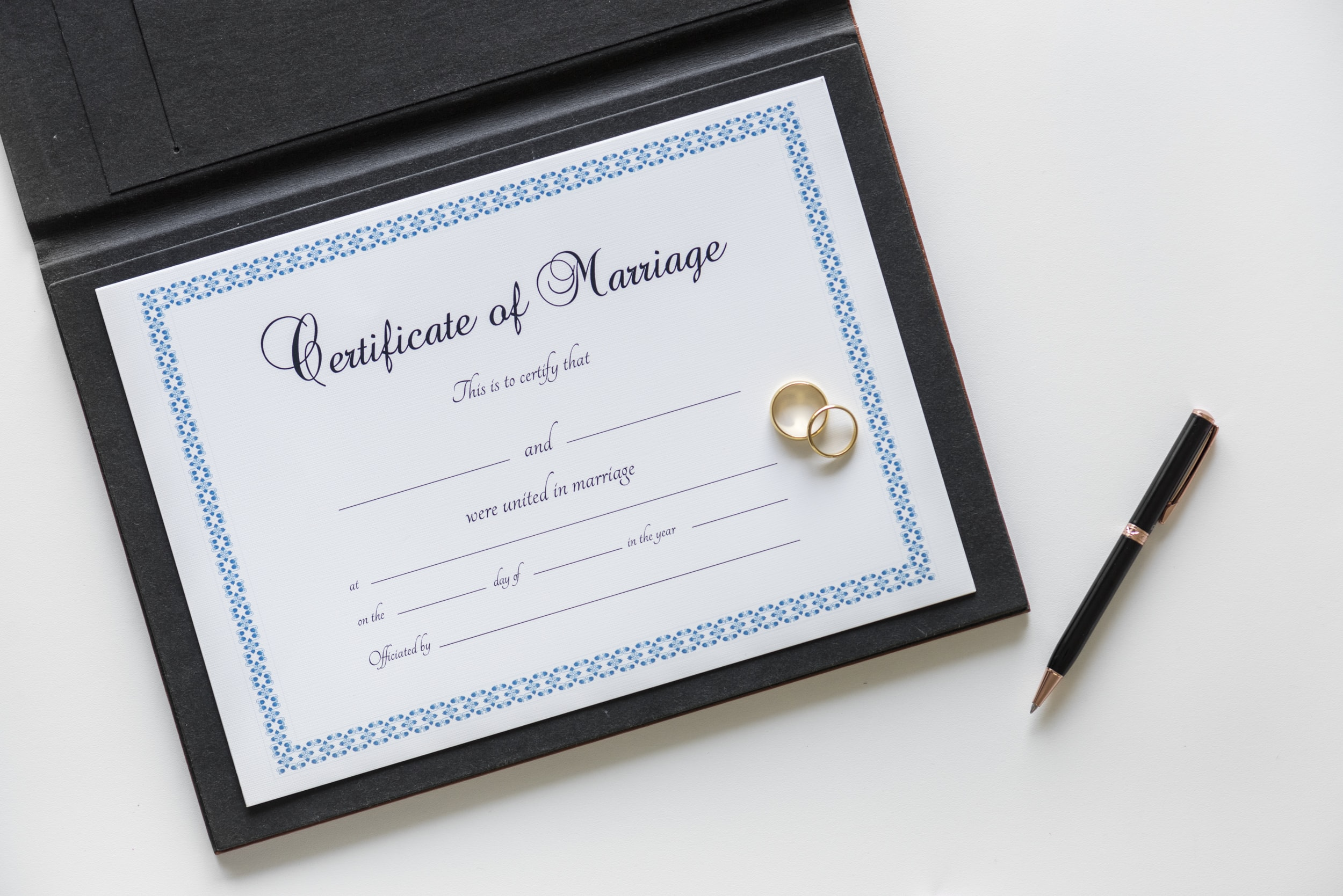 certificate of marriage with gold-colored wedding rings beside black click pen