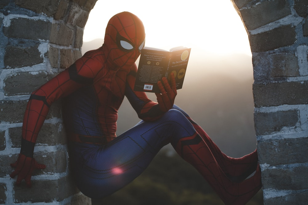 Spider-Man leaning on concrete brick while reading book