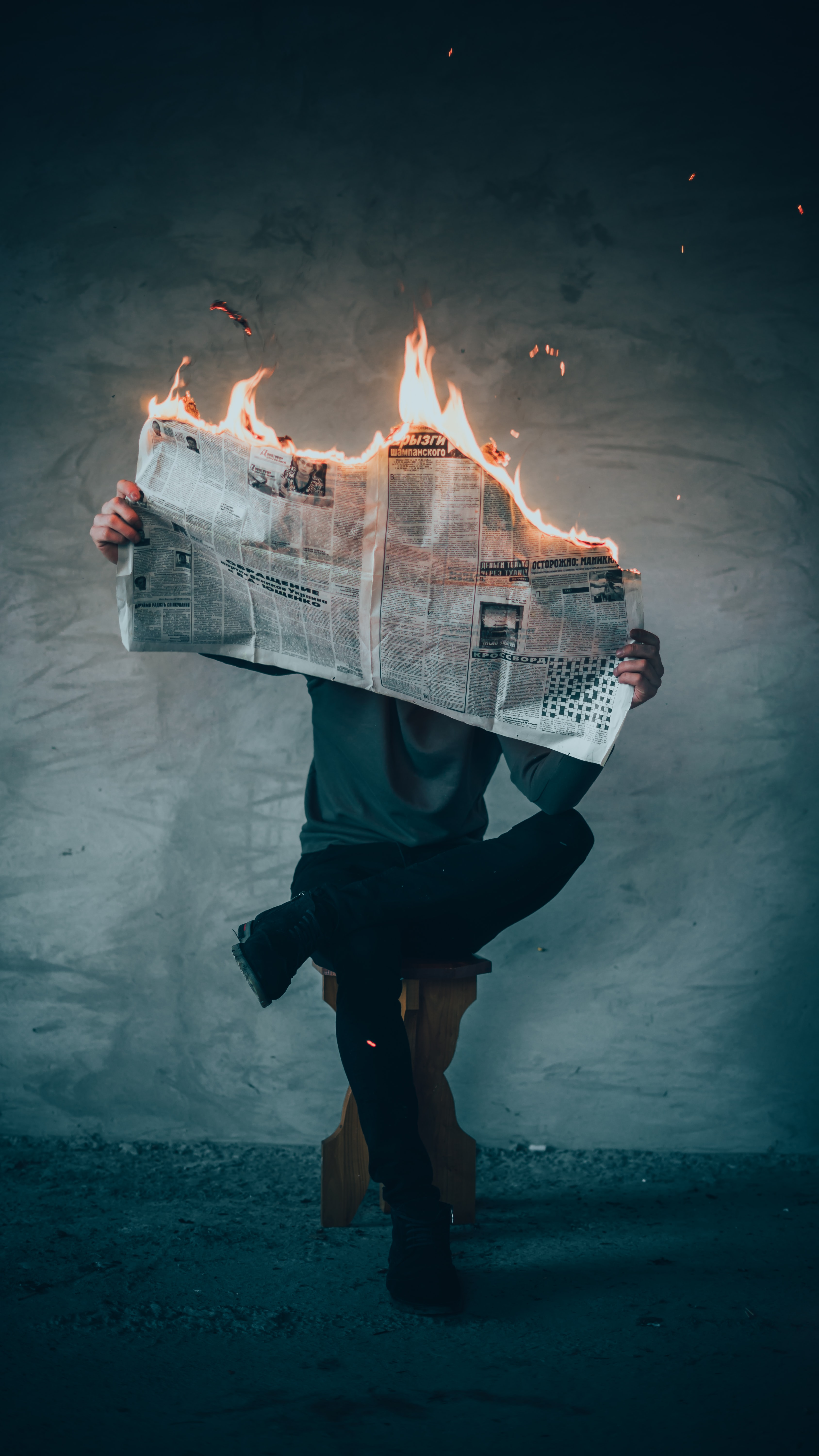 surrealism photography of person reading news paper in fire while sitting on stool