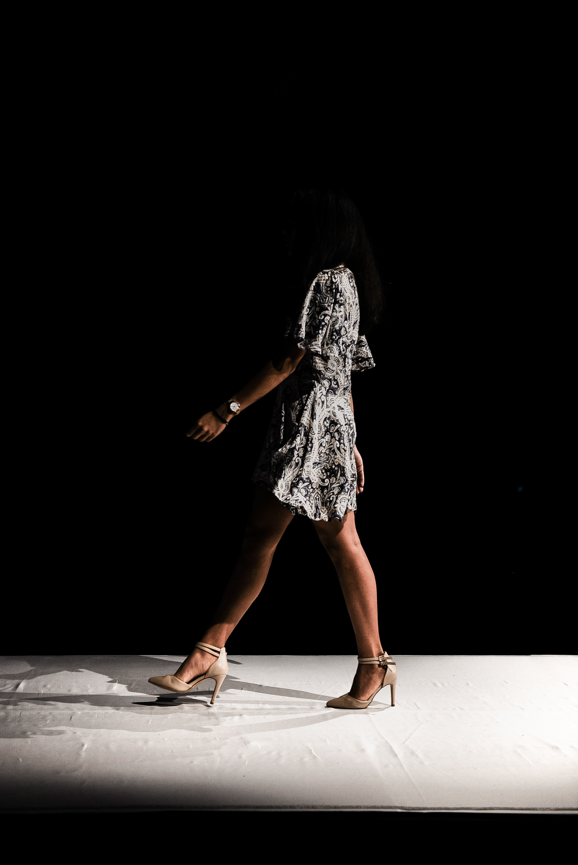 woman wearing black and white floral dress walks inside dark room