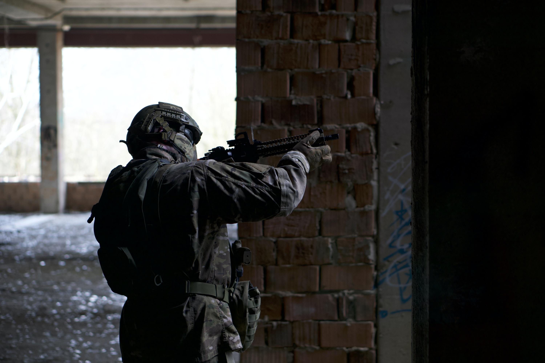 man holding rifle beside wall