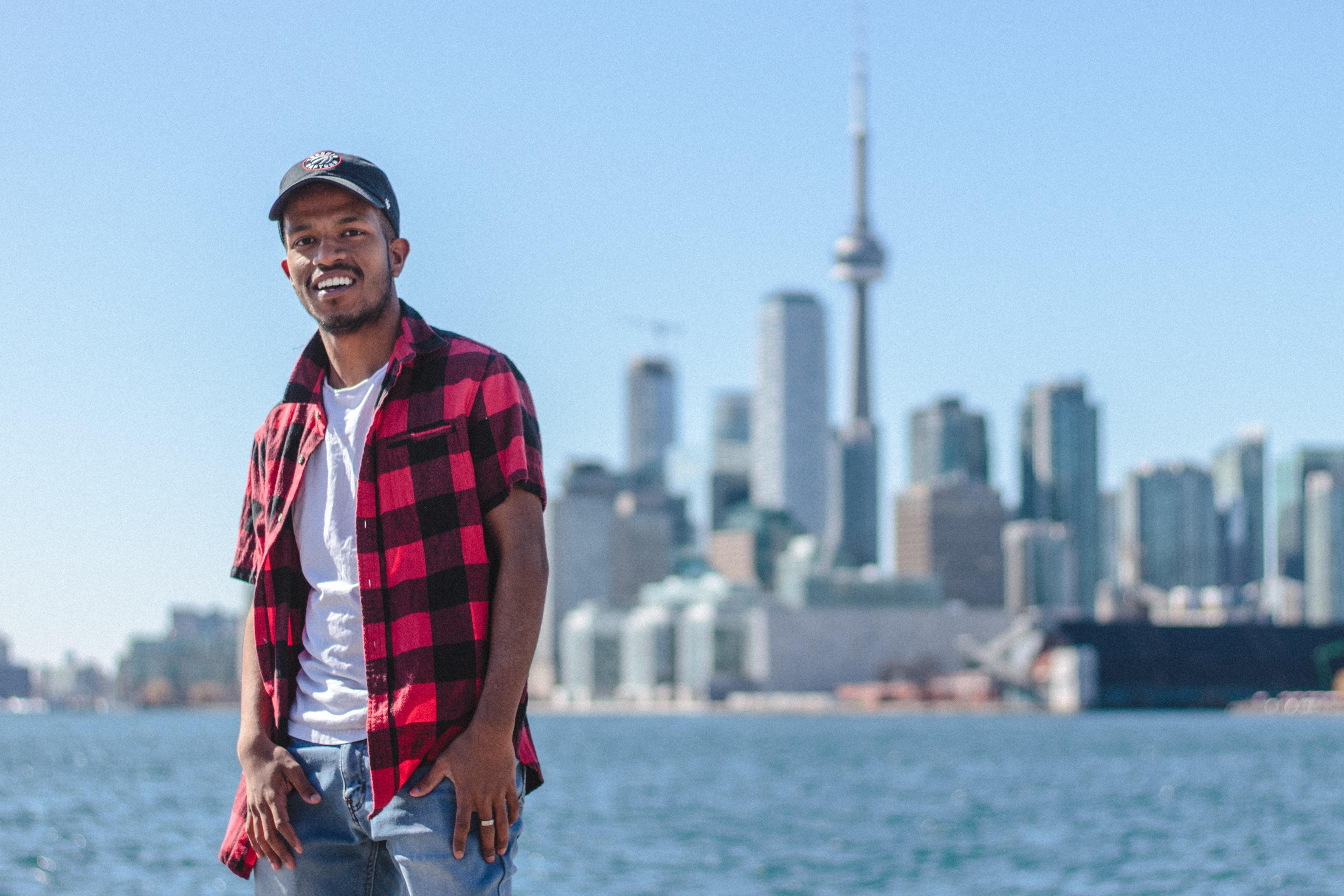 standing man taking selfie beside CN Tower, Canada