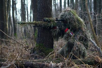 person holding green rifle shooting army zoom background