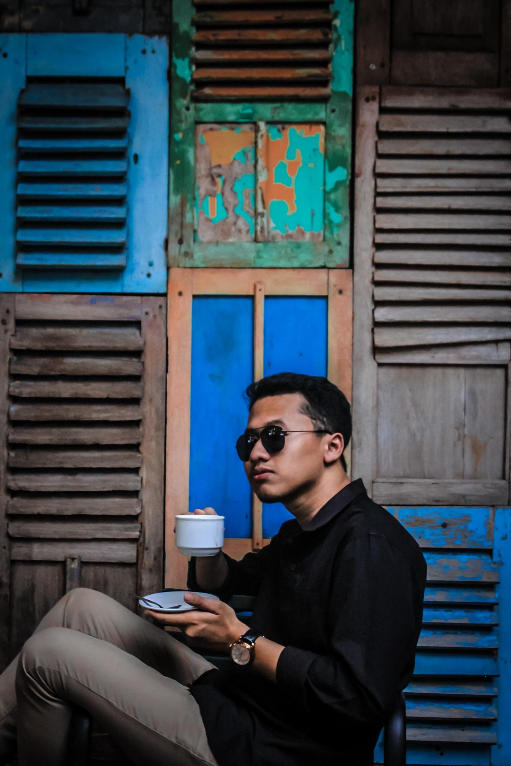man in black dress shirt holding saucer and mug