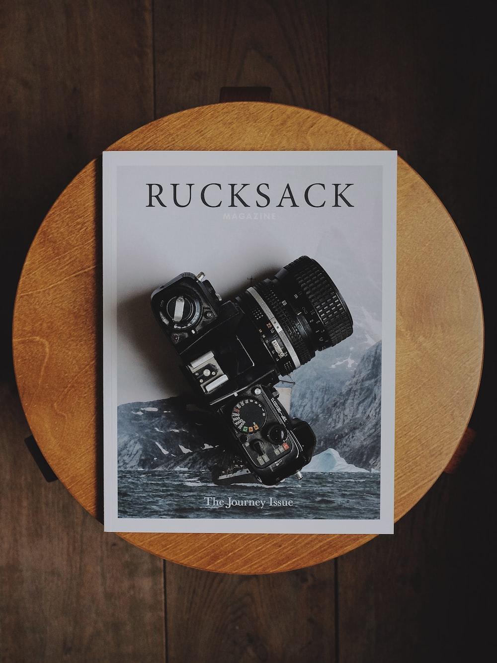 black DSLR camera on Rucksack book