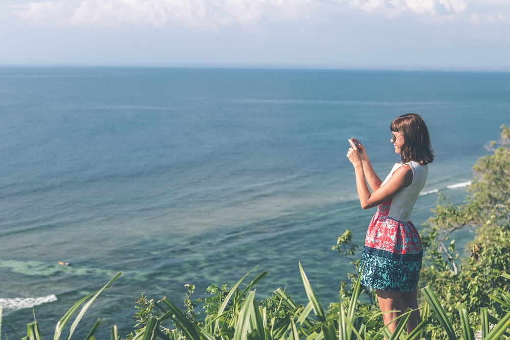 woman taking photo of ocean atop a cliff during day time