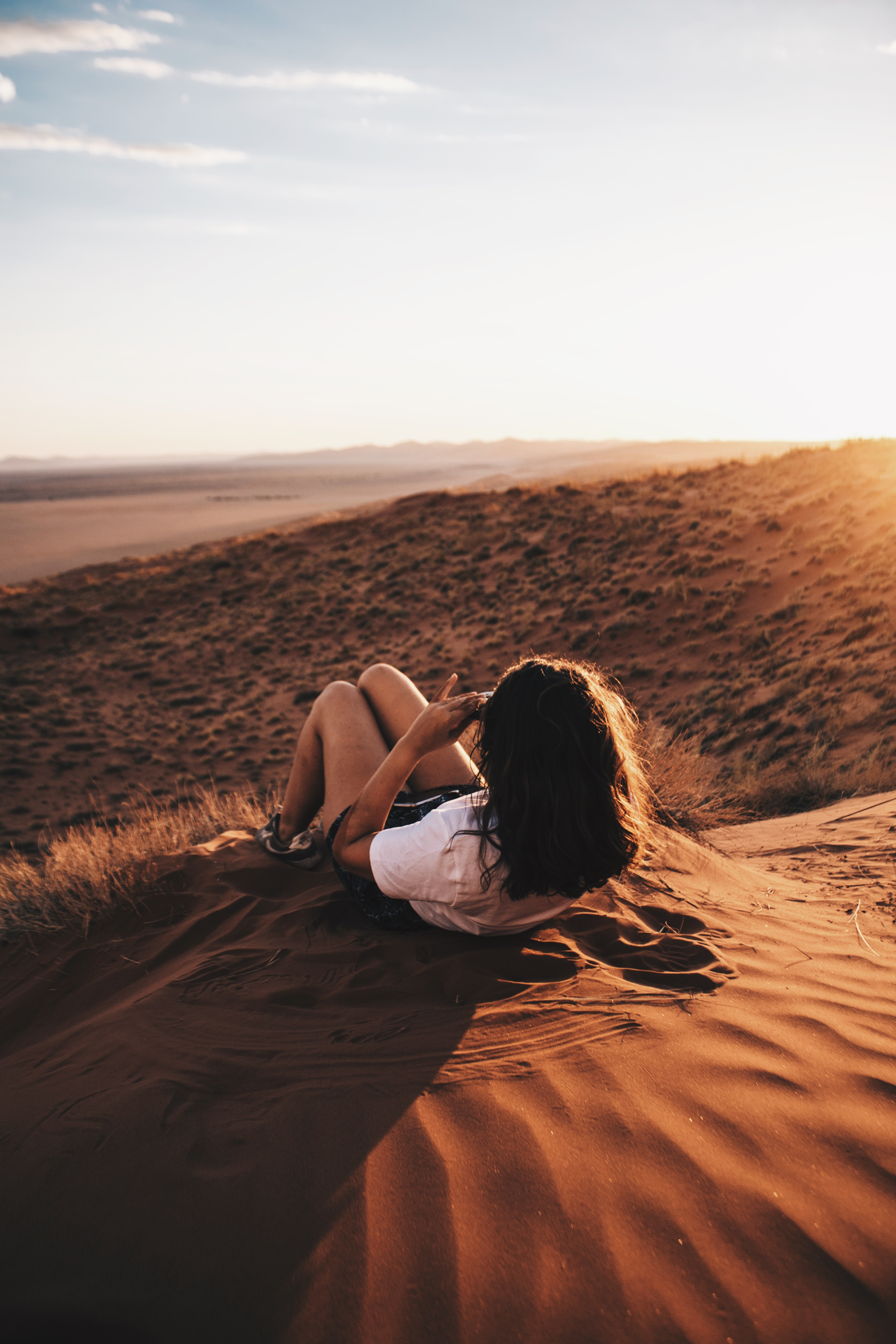 woman lying on sand during daytime