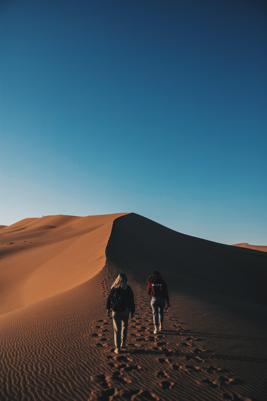 two women walking on desert