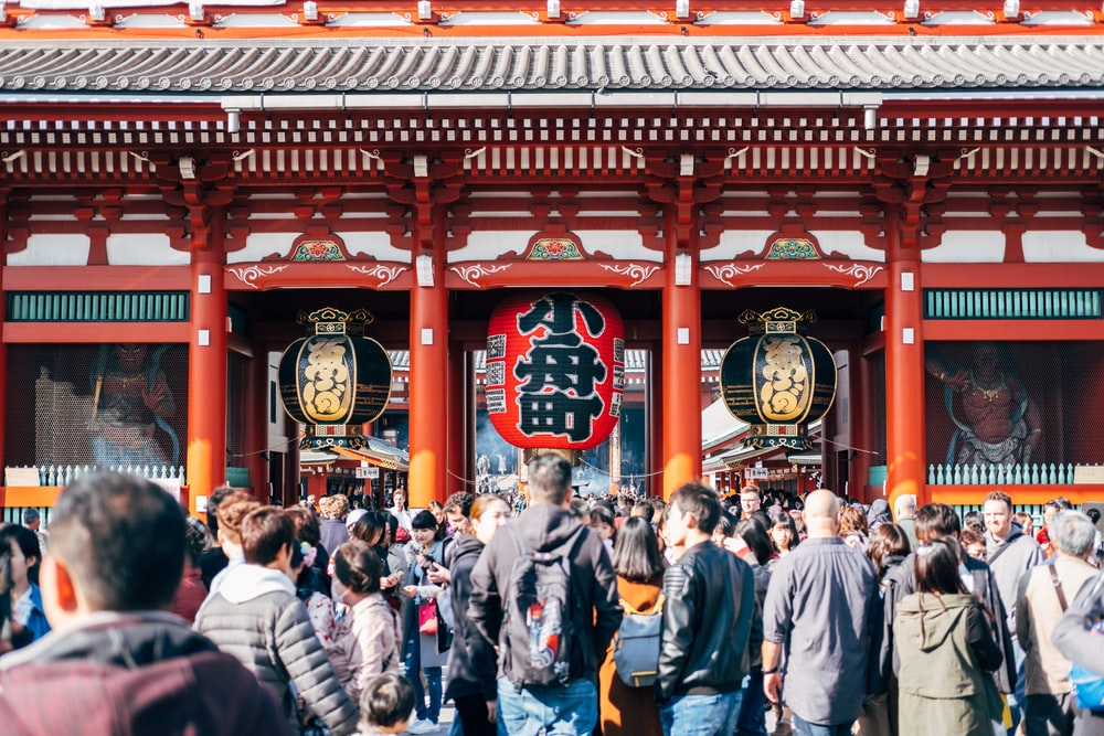 group of people standing near Chinese temple during daytime