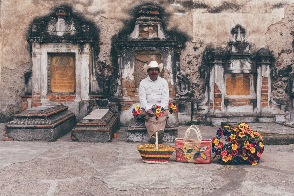 man sitting on tombstone