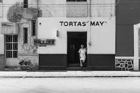 man standing on Tortas May storefront during daytime