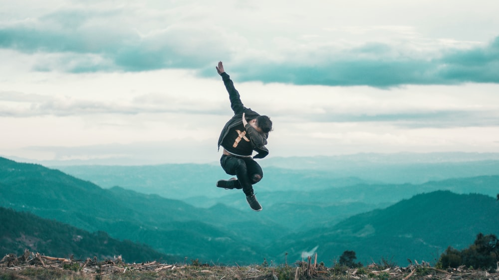 photo of man in jacket and pants jumping while posing