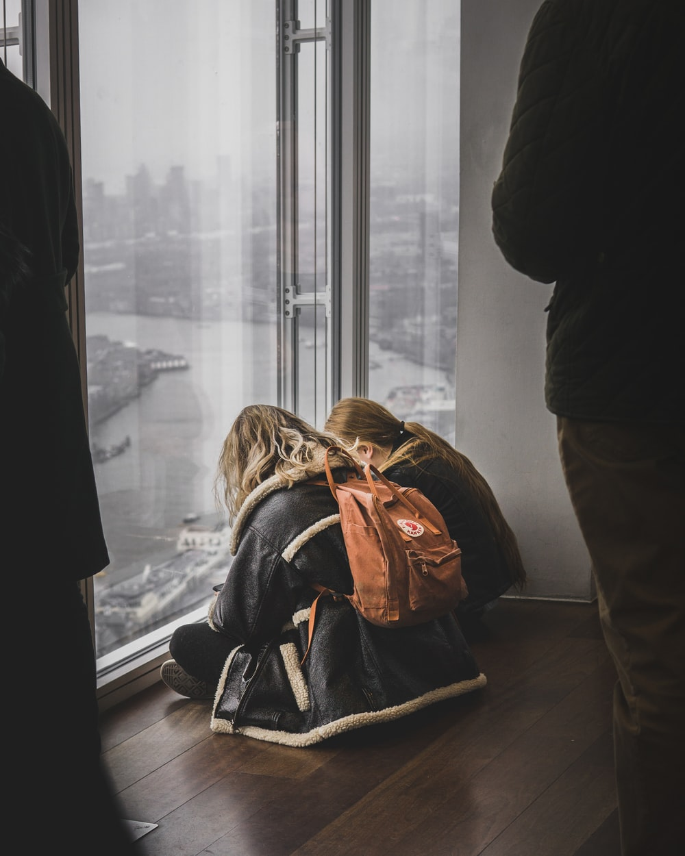 two woman sitting in front of glass panel
