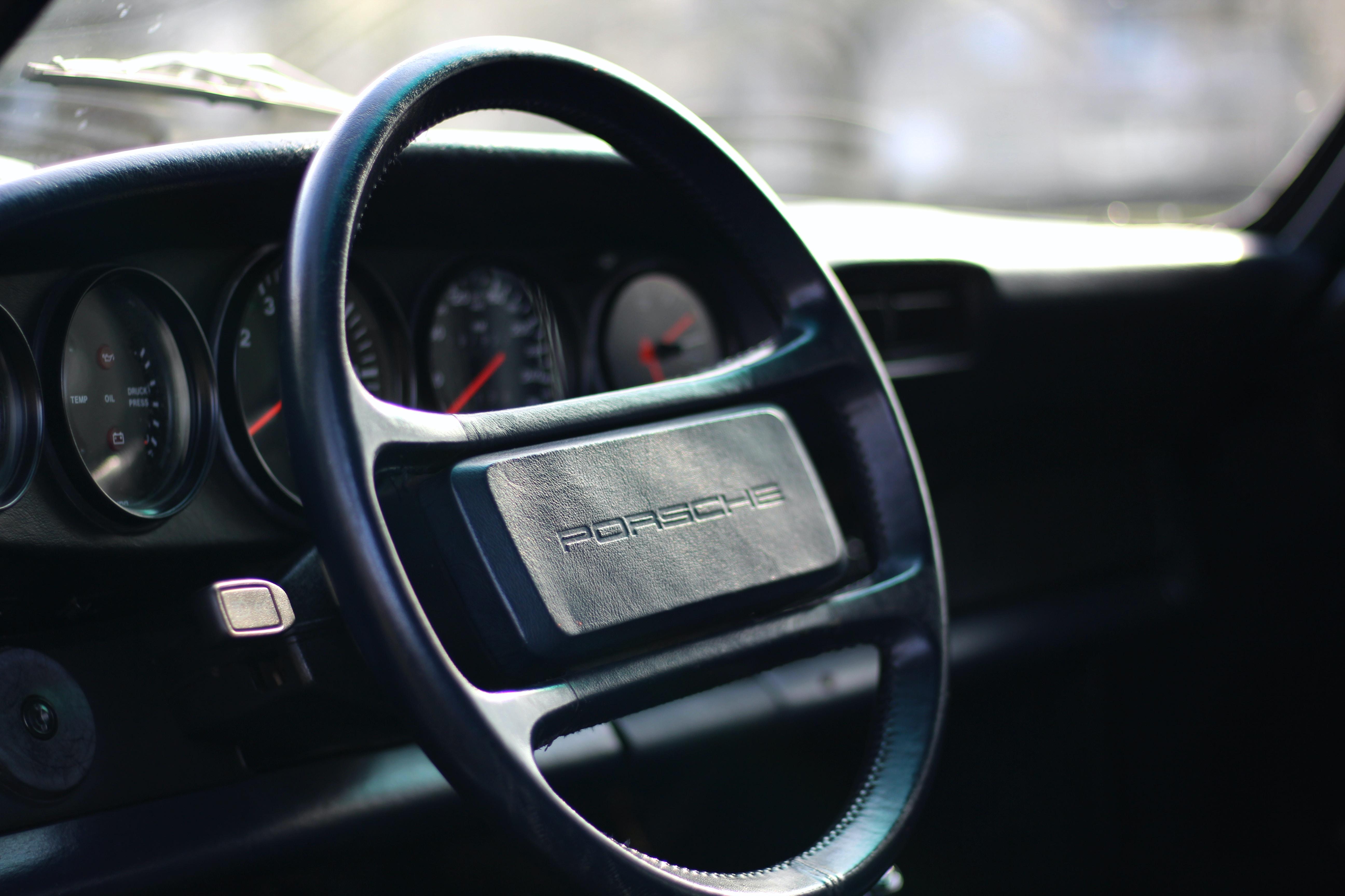 selective focus photography of black Porsche steering wheel