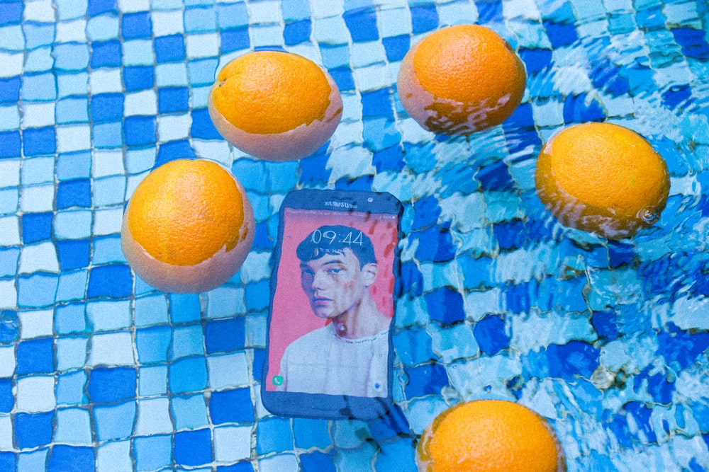 five orange fruits and one black smartphone on water