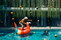person standing on inflatable duck on swimming pool during daytime