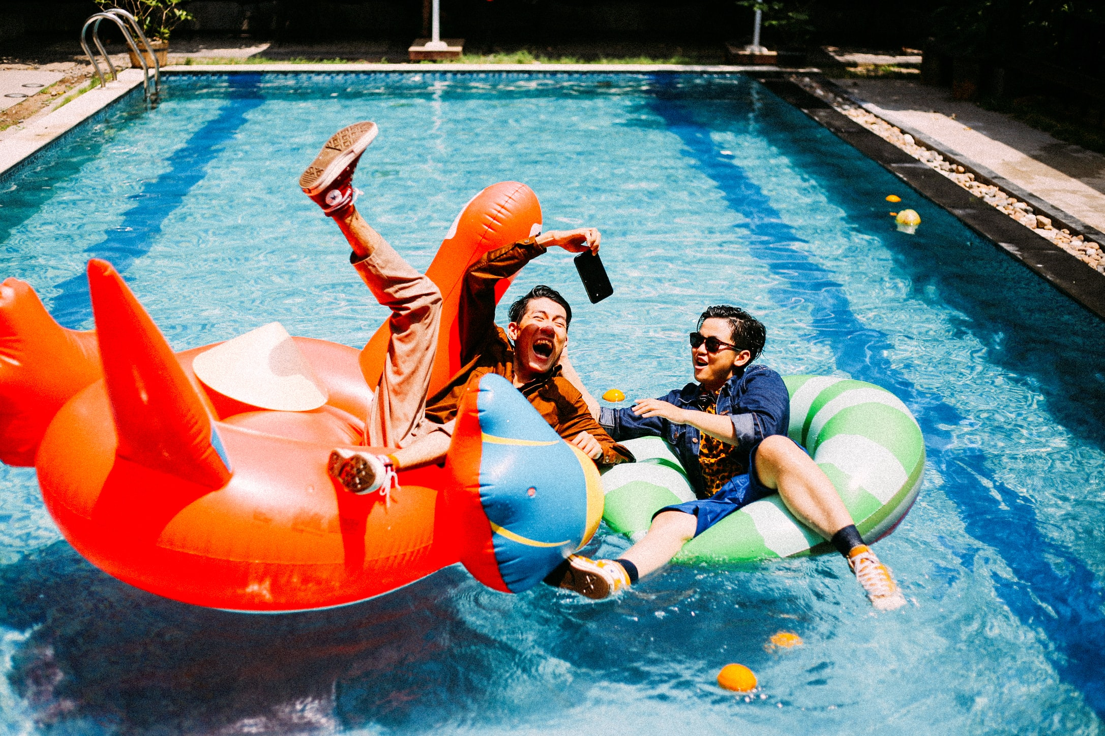 two man on red and green inflatable swim rim during day time
