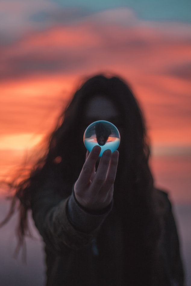 A photo of a woman in silhouette at sunset, holding a crystal ball in front of her face that catches the light.