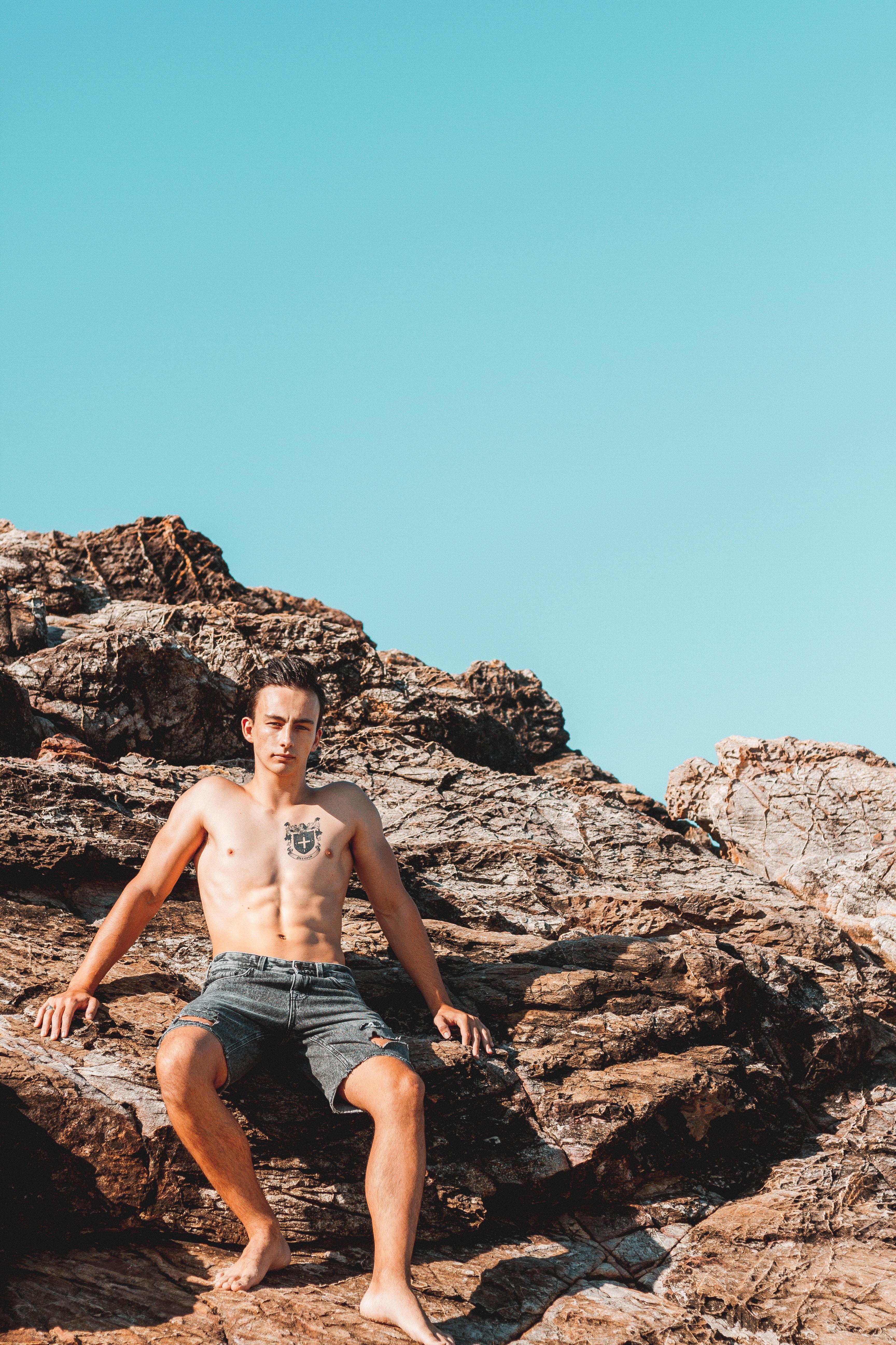 man sitting on rock fragment during daytime