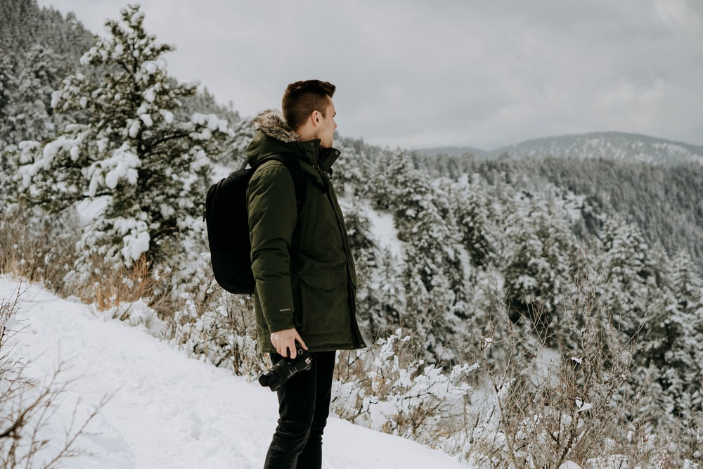 man standing on snow-covered land during daytime