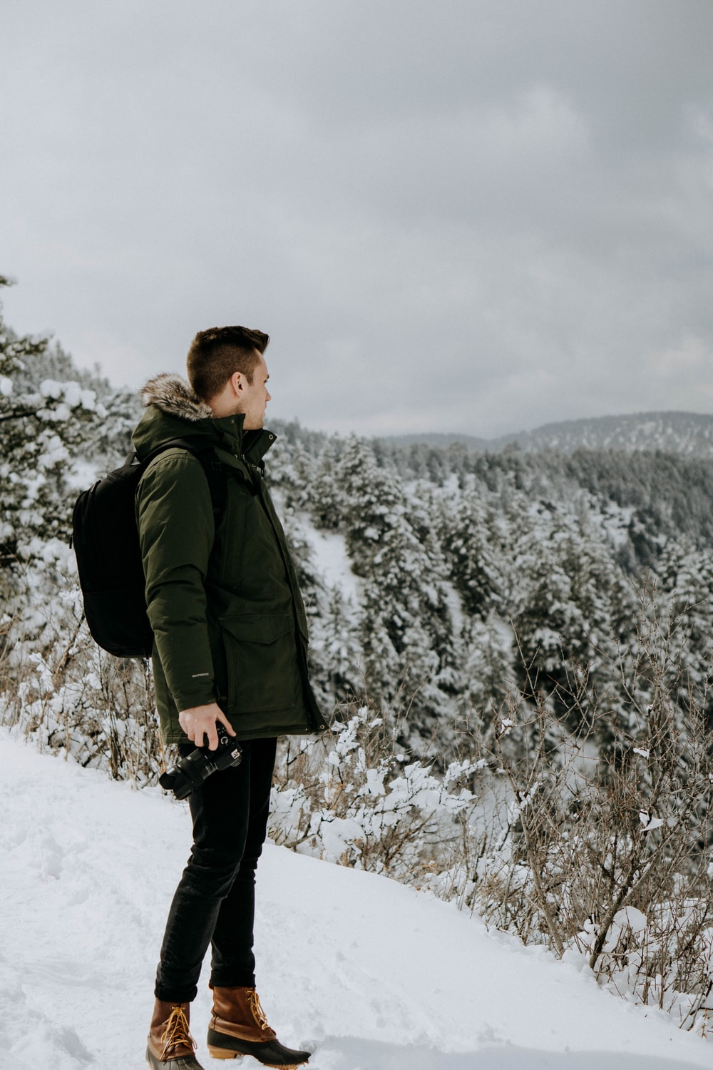 man standing on snow looking at trees under cloudy sky