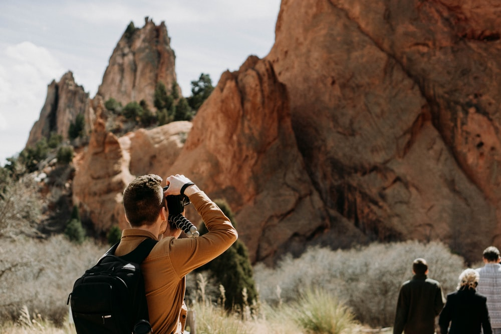 man taking photo of rock formation