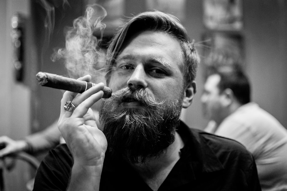 grayscale portrait photography of person smoking cigar