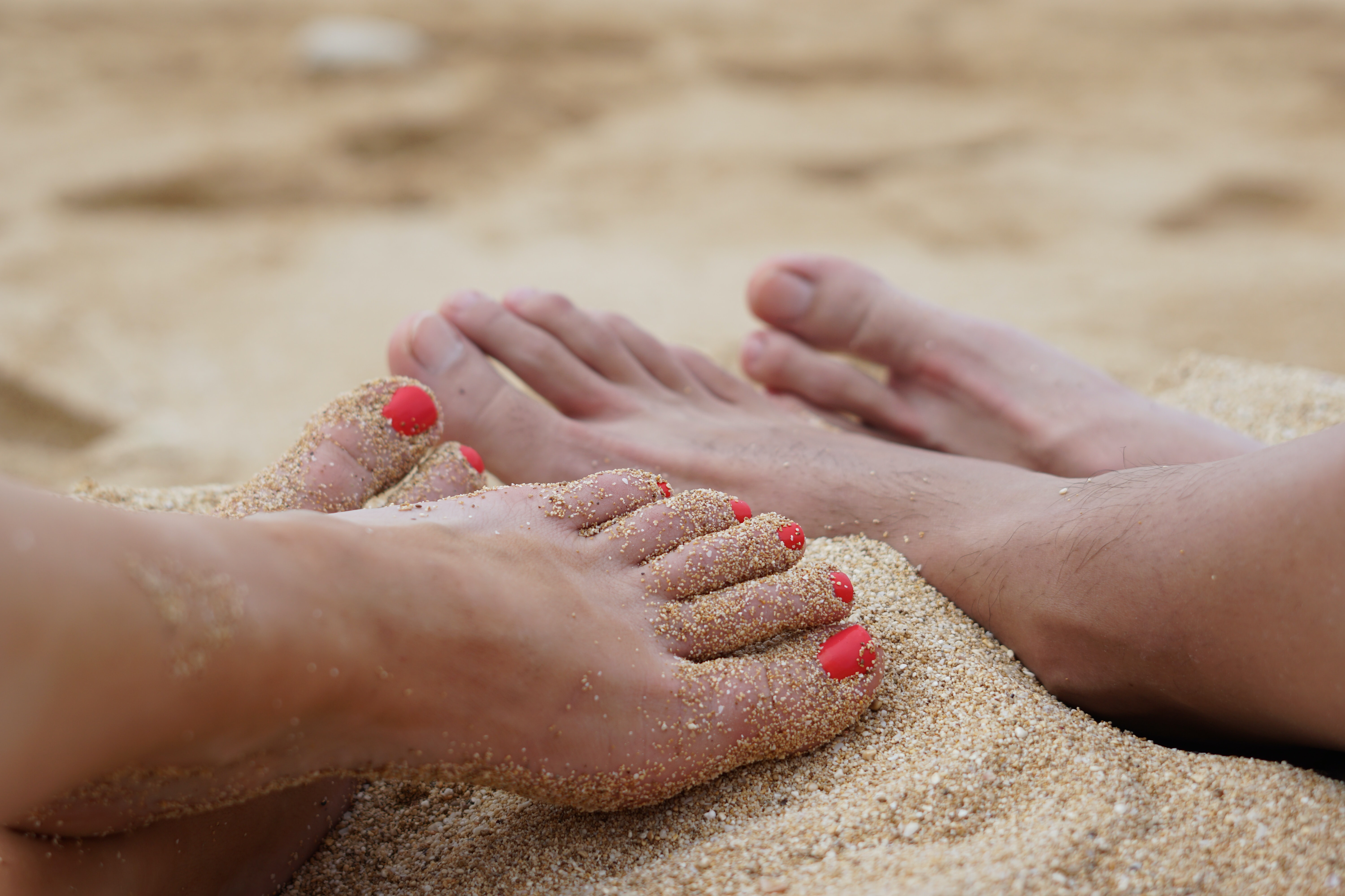 two people's feet in sand