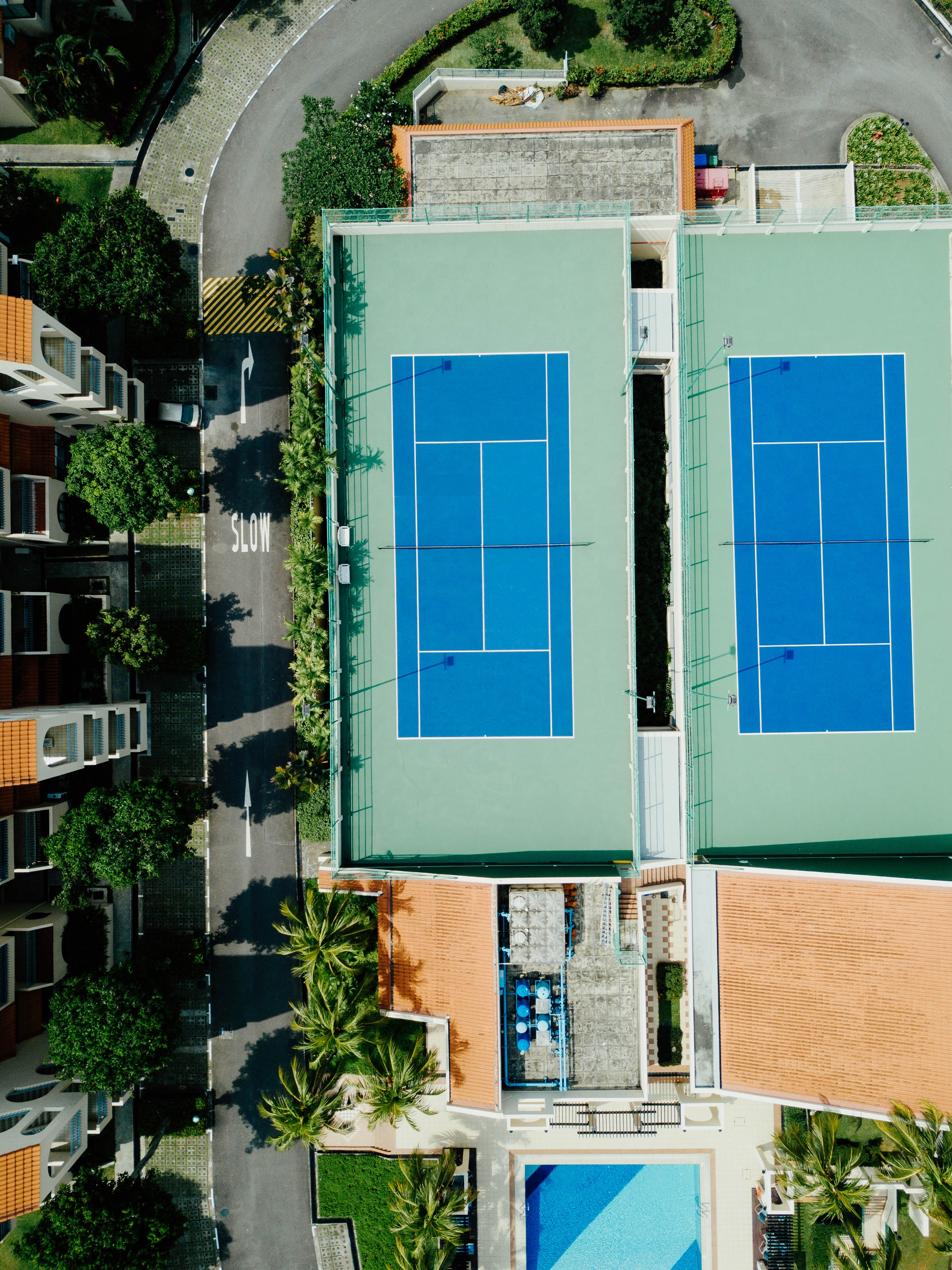 aerial photography of two badminton courts beside road during daytime