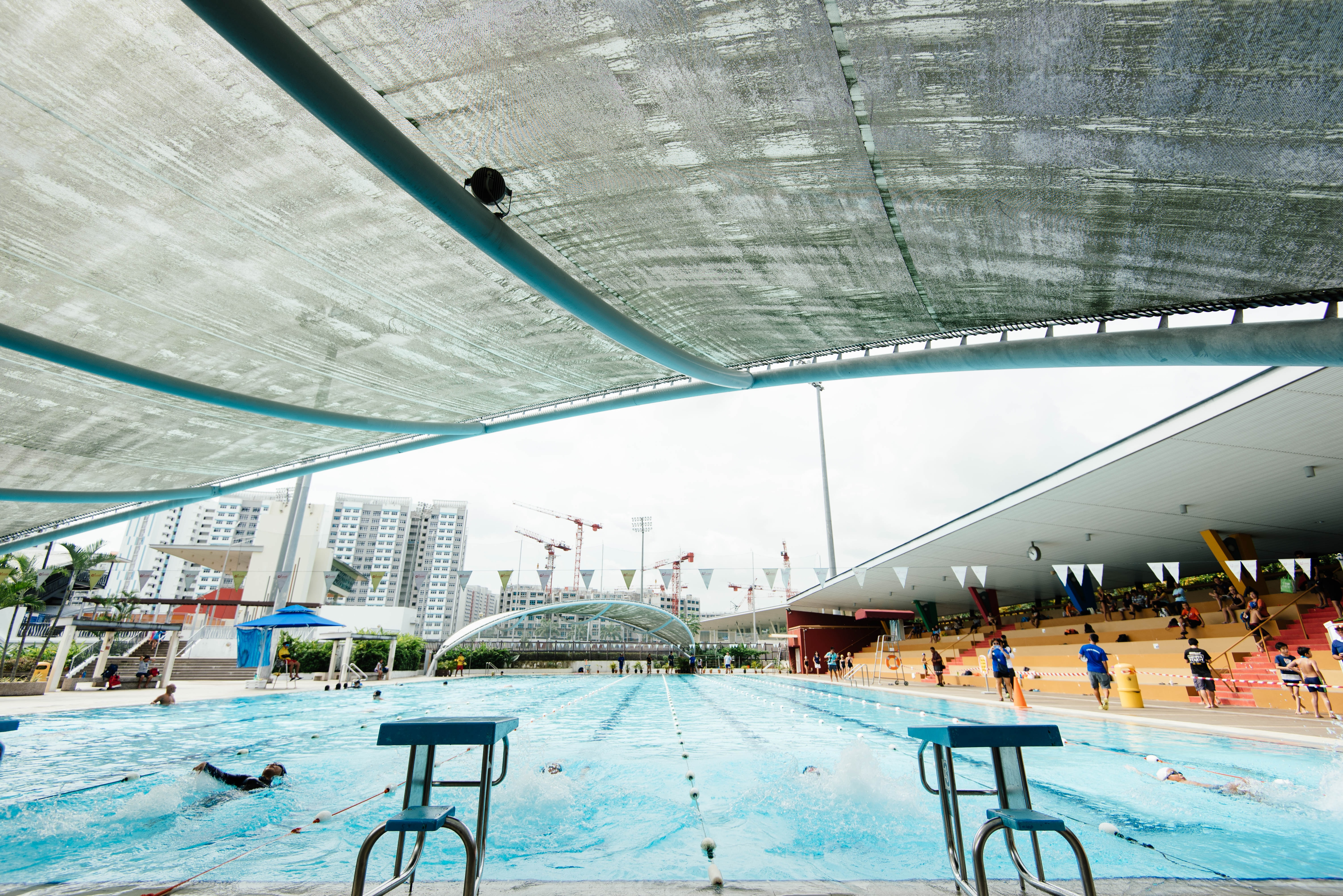 people gathering around in an olympic pool during day time