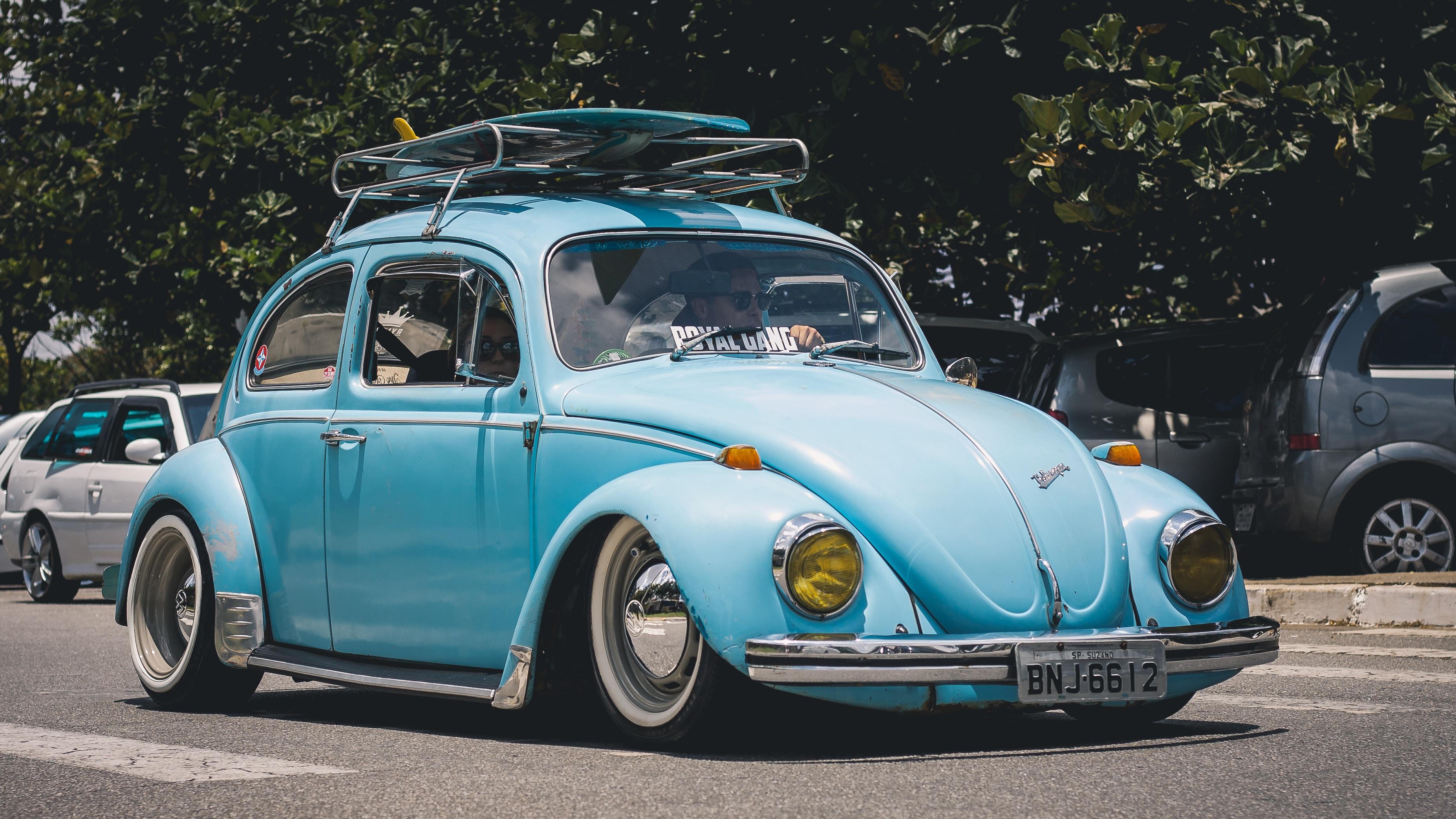 blue Volkswagen Beetle on road