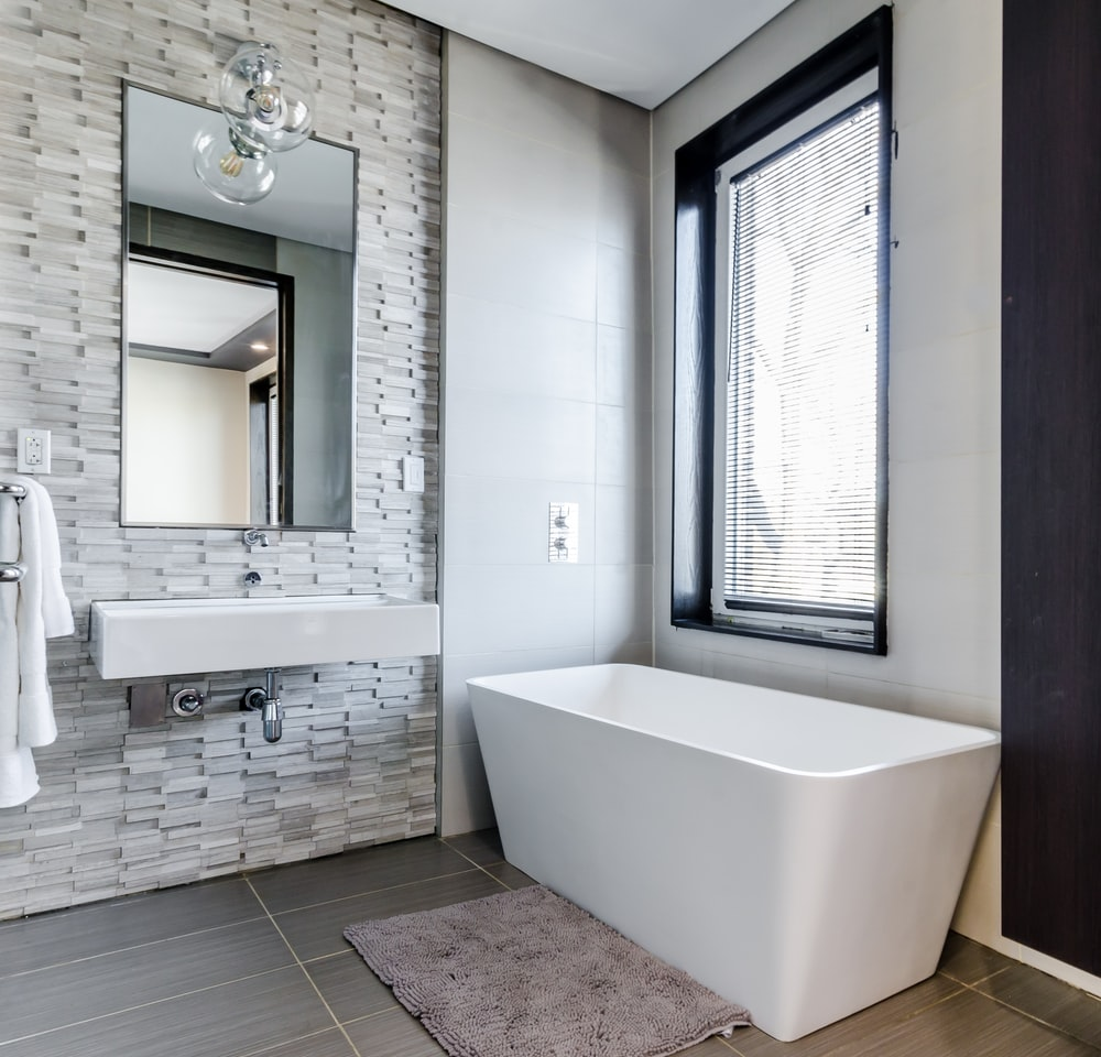 white ceramic bathtub near white framed window