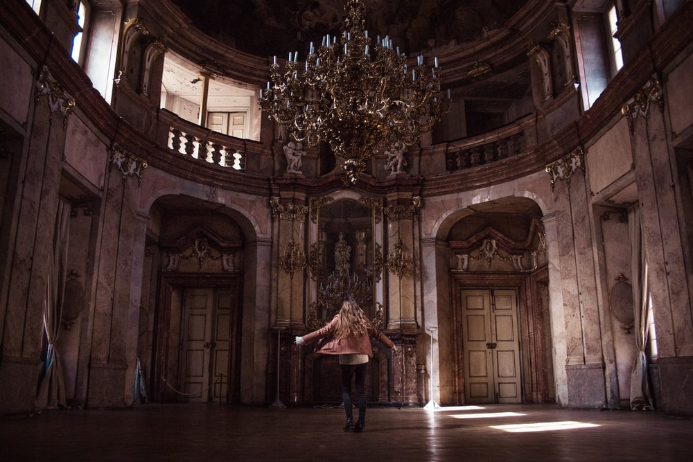 woman standing under gold chandelier indoors